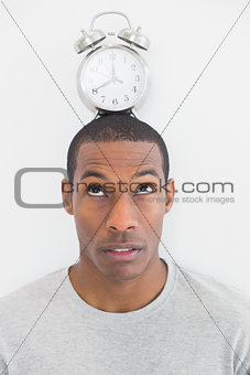Close up of a man with an alarm clock on top of his head