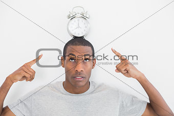 Close up of a man pointing at alarm clock over his head