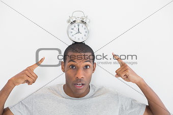 Close up portrait of a man pointing at alarm clock over his head
