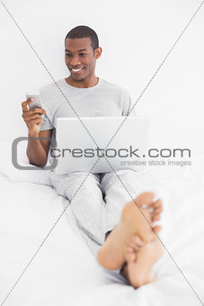 Afro man text messaging while using laptop in bed