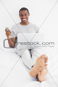 Afro young man text messaging while using laptop in bed