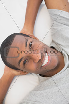 Smiling young Afro man resting in bed