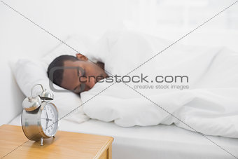 Afro man sleeping in bed with alarm clock in foreground