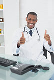 Doctor with computer while gesturing thumbs up at medical office
