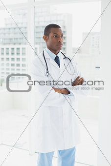 Doctor standing with arms crossed in a medical office