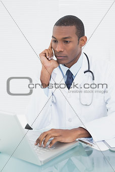 Doctor using laptop at medical office