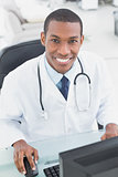 Smiling doctor using computer at medical office