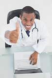 Smiling male doctor with laptop gesturing thumbs up