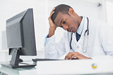 Worried male doctor using computer