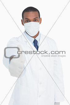 Portrait of male doctor in mask gesturing thumbs up