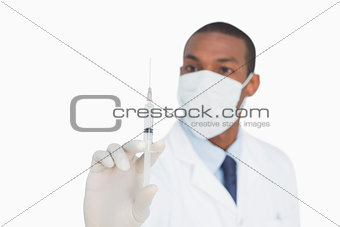 Male doctor in mask and glove holding an injection