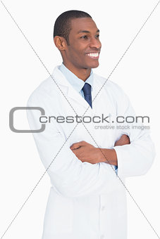Smiling male doctor standing with arms crossed