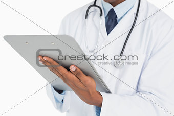 Close up mid section of a male doctor writing on clipboard