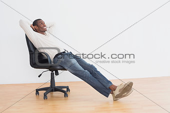 Thoughtful casual man sitting on office chair in empty room