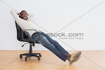 Casual Afro young man sitting on office chair in an empty room