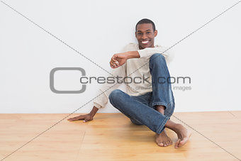 Afro young man sitting on floor in an empty room