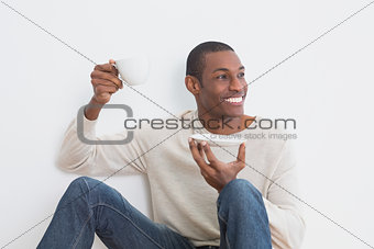 Casual Afro man having tea against wall