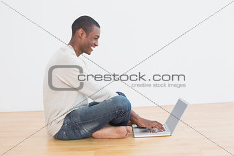 Casual Afro man using laptop on floor in an empty room