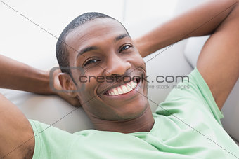 Close up of smiling relaxed Afro man lying on sofa
