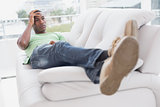 Thoughtful relaxed young Afro man lying on sofa