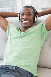 Relaxed Afro man with headphones sitting on sofa