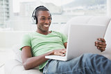 Smiling Afro man with headphones using laptop on sofa
