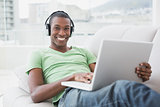 Portrait of smiling Afro man with headphones using laptop on sofa