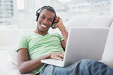 Relaxed smiling Afro man with headphones using laptop on sofa