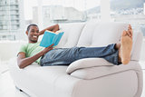 Full length of smiling Afro man reading a book on sofa