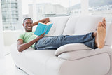 Full length portrait of smiling Afro man reading a book on sofa