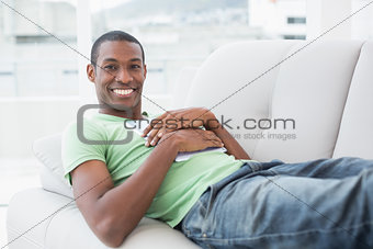 Casual smiling Afro man with digital tablet lying on sofa