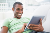 Casual smiling Afro man using digital tablet on sofa