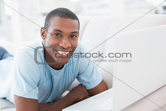 Smiling Afro man with laptop lying on sofa