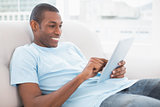 Casual smiling young Afro man using digital tablet on sofa