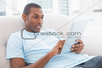 Casual young Afro man using digital tablet on sofa