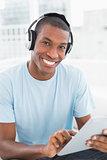 Afro man wearing headphones while using digital tablet