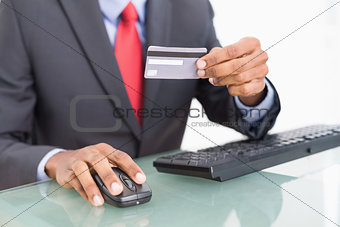 Close up mid section of a businessman doing online shopping