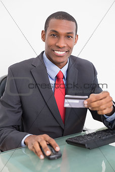 Smiling Afro businessman doing online shopping