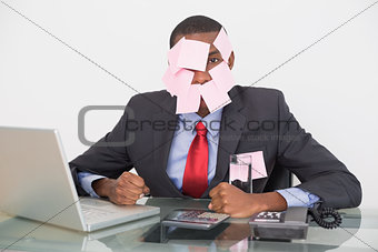 Afro businessman with blank notes on face and laptop