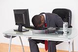 Afro businessman resting head on keyboard in office