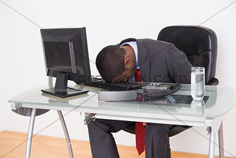 Afro businessman resting head on keyboard in office