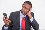 Young tensed young Afro businessman with telephone receiver