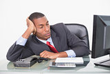 Young Afro businessman resting at desk