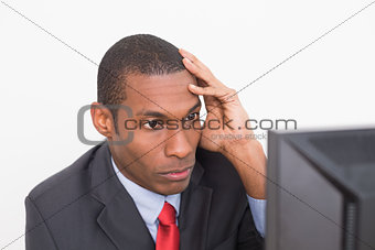 Close up of serious Afro businessman looking at computer
