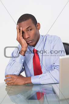 Angry Afro businessman looking at laptop at desk
