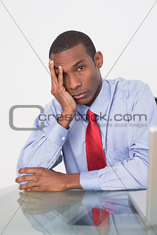 Angry Afro businessman with hand on face at desk