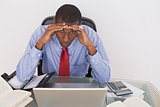 Afro businessman with head in hands at desk