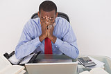 Angry Afro businessman with hands on face at desk