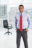 Elegant serious Afro businessman standing in office