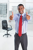 Elegant Afro businessman gesturing thumbs up in office